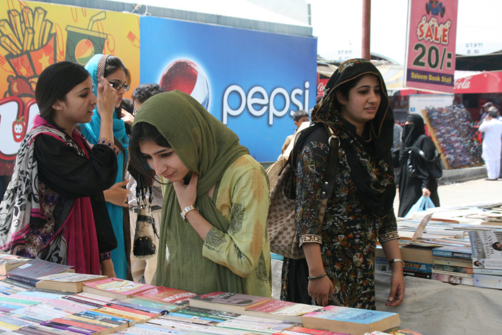 Women look over the titles of books at an outdoor market in Karachi, Pakistan's most populous city. Photo by Larisa Epatko