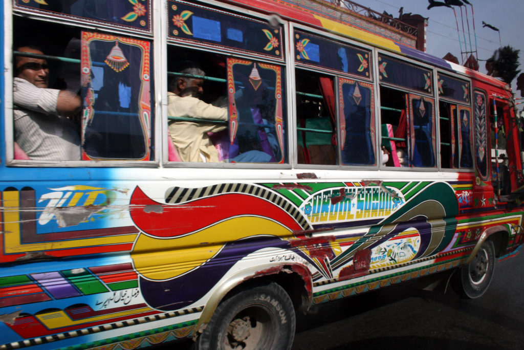 A psychedelic bus rumbles by in busy Karachi. Pakistan has a population of about 204 million with about 21 million in the coastal city of Karachi. Photo by Larisa Epatko