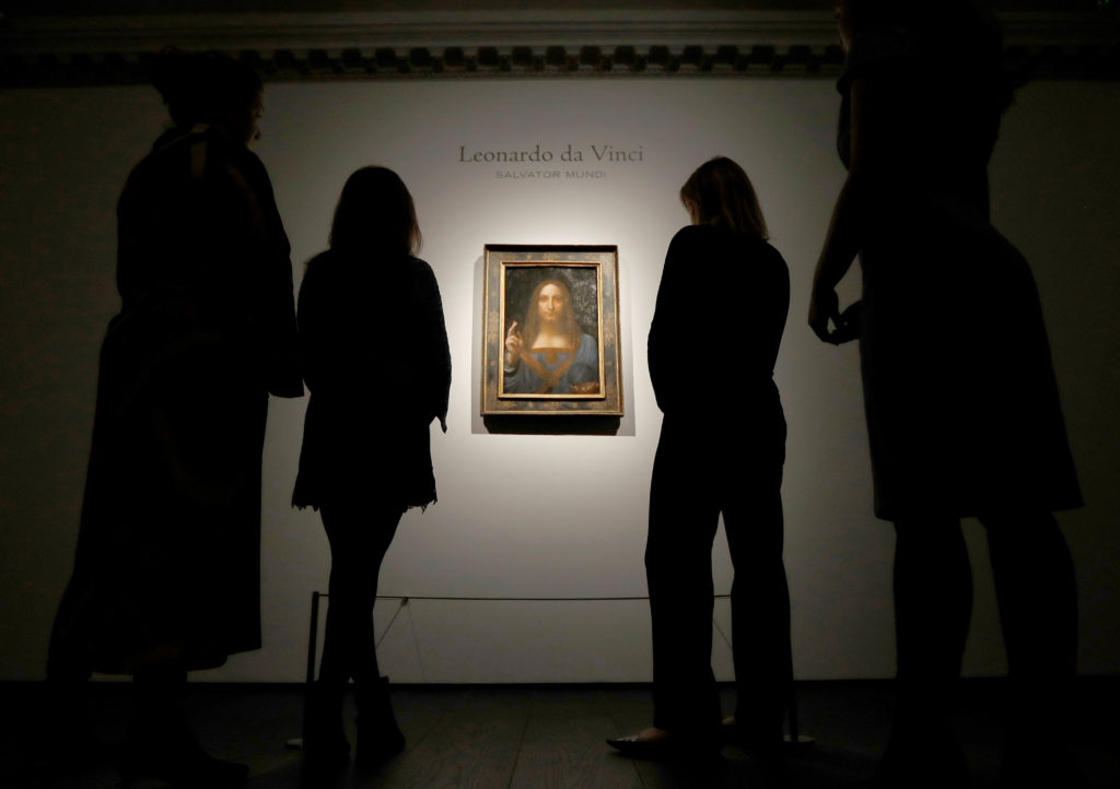 """FILE PHOTO: Members of Christie's staff pose for pictures next to Leonardo da Vinci's """"Salvator Mundi"""" painting which will be auctioned by Christie's in New York in November, in London, Britain October 24, 2017. REUTERS/Peter Nicholls/File photo NO RESALES. NO ARCHIVES - RC118A603C00"""