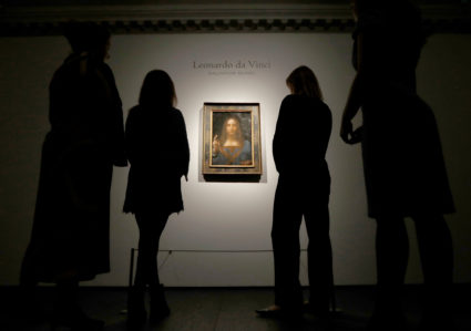 "FILE PHOTO: Members of Christie's staff pose for pictures next to Leonardo da Vinci's ""Salvator Mundi"" painting which will be auctioned by Christie's in New York in November, in London, Britain October 24, 2017. REUTERS/Peter Nicholls/File photo NO RESALES. NO ARCHIVES - RC118A603C00"