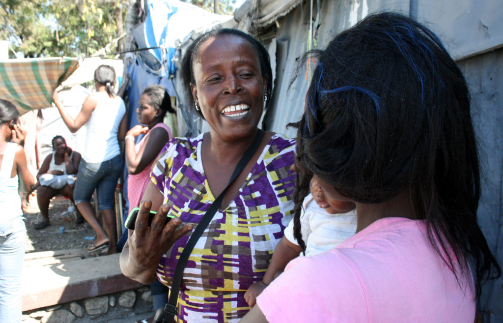 KOFAVIV community agent Georgette Etienne speaks to a woman in the Champs de Mars tent camp in Port-au-Prince, Haiti. Photo by Larisa Epatko