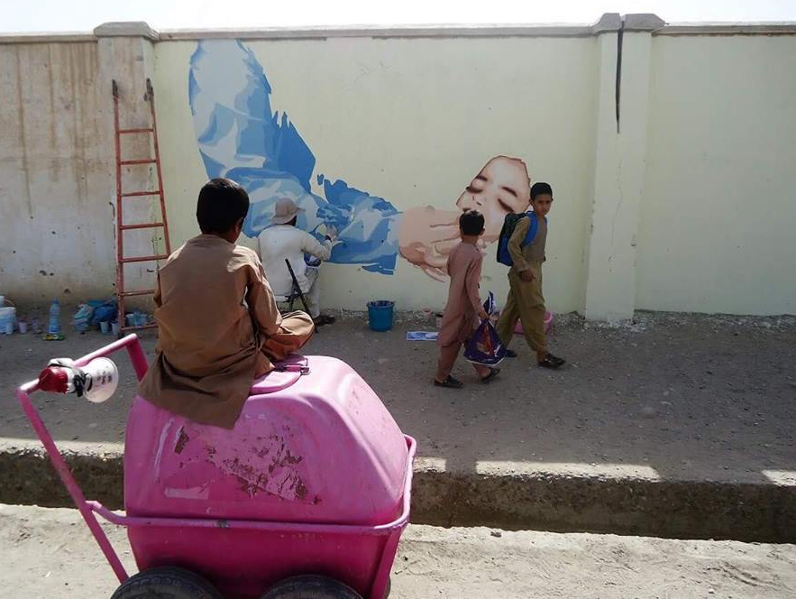 Children watch as painters depict a polio vaccination campaign. Photo courtesy of ArtLords