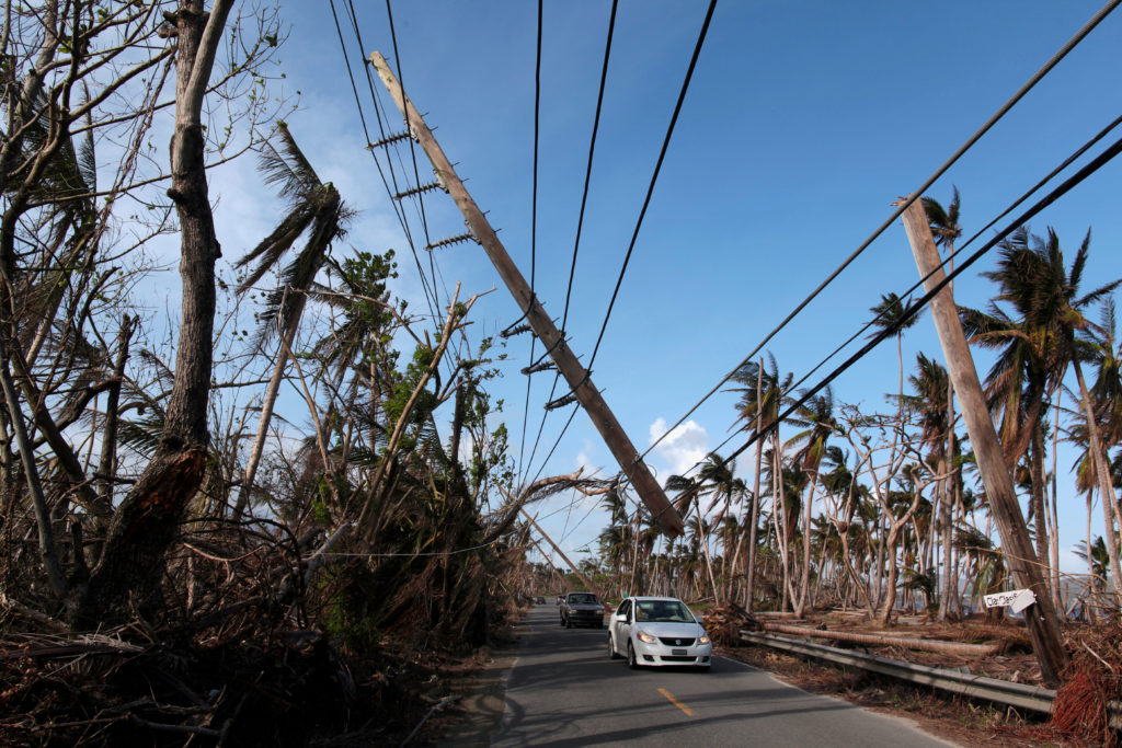 Cars drive under a partially collapsed utility pole, after the island was hit by Hurricane Maria in September, in Naguabo, Puerto Rico October 20, 2017. Photo by Alvin Baez/REUTERS
