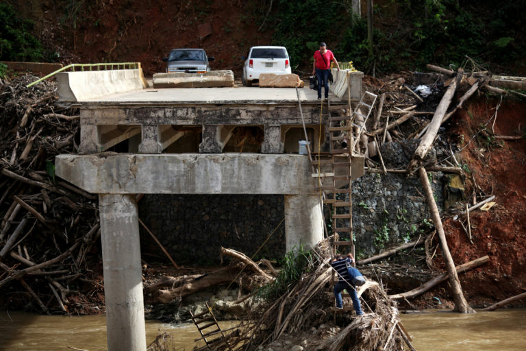 A woman looks as her husband climbs down a ladder at a partially destroyed bridge, after Hurricane Maria hit the area in September, in Utuado, Puerto Rico November 9, 2017. Picture taken November 9, 2017. REUTERS/Alvin Baez TPX IMAGES OF THE DAY - RC14D74F7730