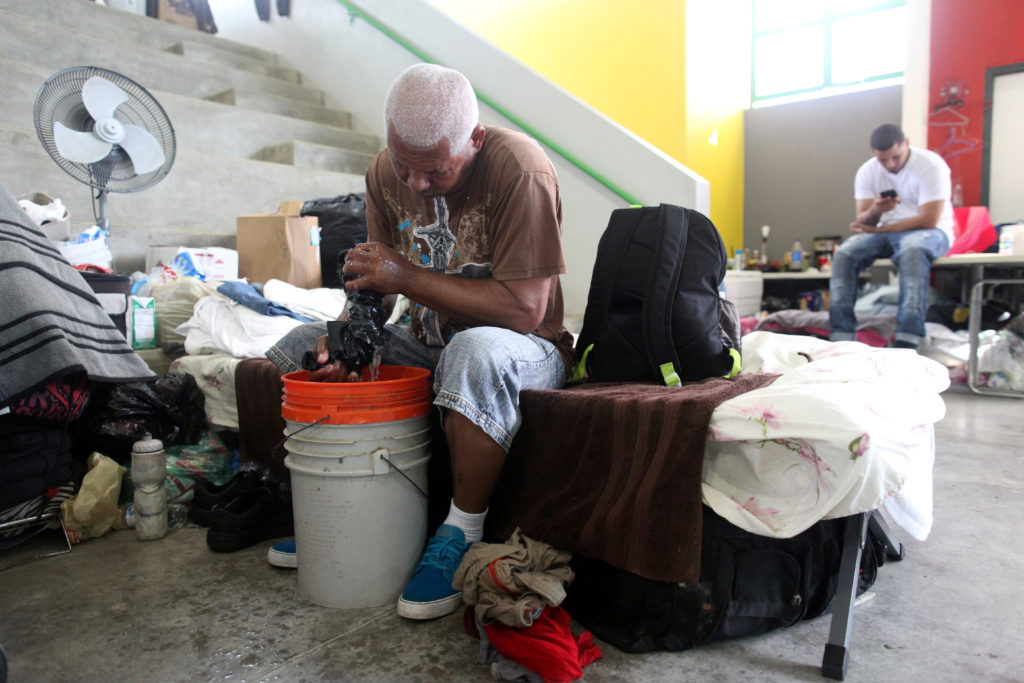 A man does his laundry while sitting on a cot at a school turned shelter after he lost his home during Hurricane Maria in September as former U.S. President Bill Clinton (not pictured) visits, in Canovanas, Puerto Rico November 20, 2017. REUTERS/Alvin Baez - RC124BEA1A20