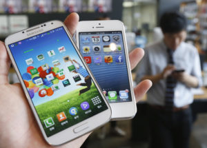 Samsung Electronics' Galaxy S4 (L) and Apple's iPhone 5 are seen in this picture illustration taken in Seoul, South Korea May 13, 2013. REUTERS/Kim Hong-Ji/File Photo - TM3ECAB12FA01