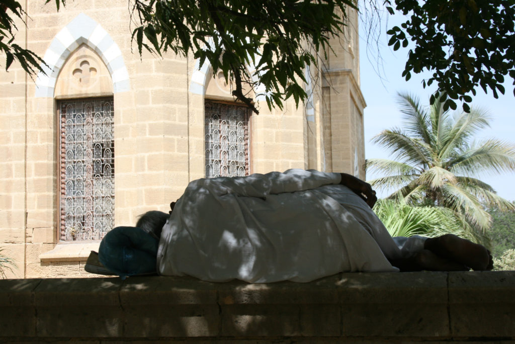 A man naps outside a mosque in Pakistan. About 96 percent of Pakistanis are Muslim. Photo by Larisa Epatko