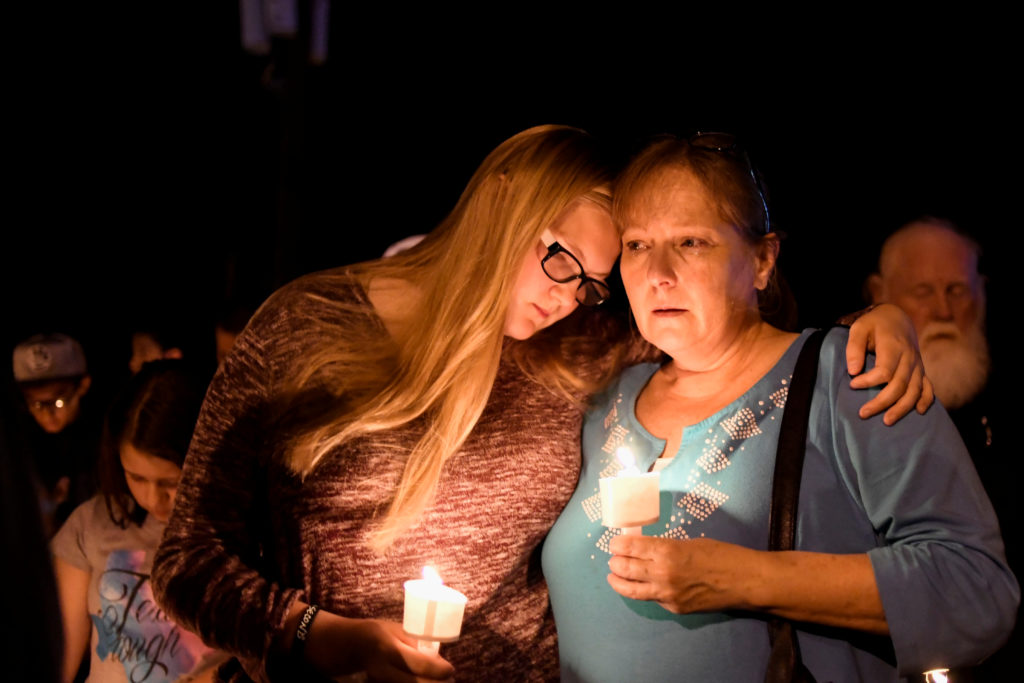Local residents embrace during a candlelight vigil for victims of a mass shooting in a church in Sutherland Springs, Texas, U.S., November 5, 2017.  REUTERS/Mohammad Khursheed - RC16204ECCD0