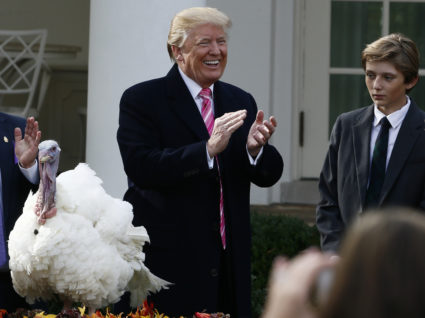 U.S. President Donald Trump laughs and applauds as he participates in the 70th National Thanksgiving turkey pardoning ceremony with his son Barron in the Rose Garden of the White House in Washington, U.S., November 21, 2017. REUTERS/Jim Bourg - HP1EDBL1GHYYZ