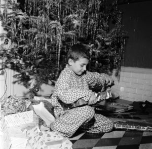 Circa 1955, a young boy sits under a Christmas tree to open his gifts. (Photo by Sherman/Three Lions/Getty Images)