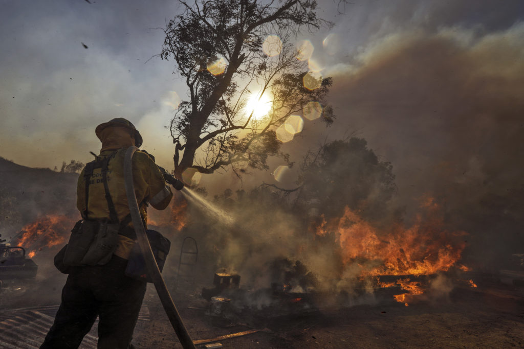 LAKE VIEW TERRACE, CA - DECEMBER 05: Firefighters try to control a pile of railroad ties and a trailer burning to protect the structure near Dexter County Park on December 5, 2017 in Lake View Terrace, California. Photo by Irfan Khan/Los Angeles Times via Getty Images