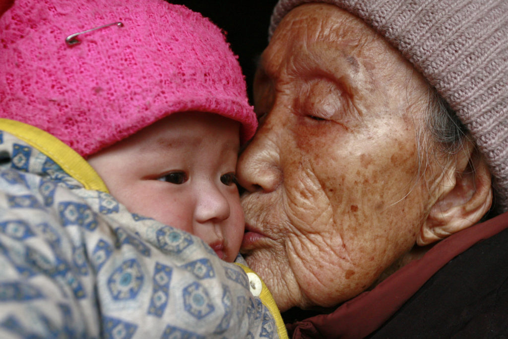 An elderly woman kisses a three-month-old baby at a village in Suining