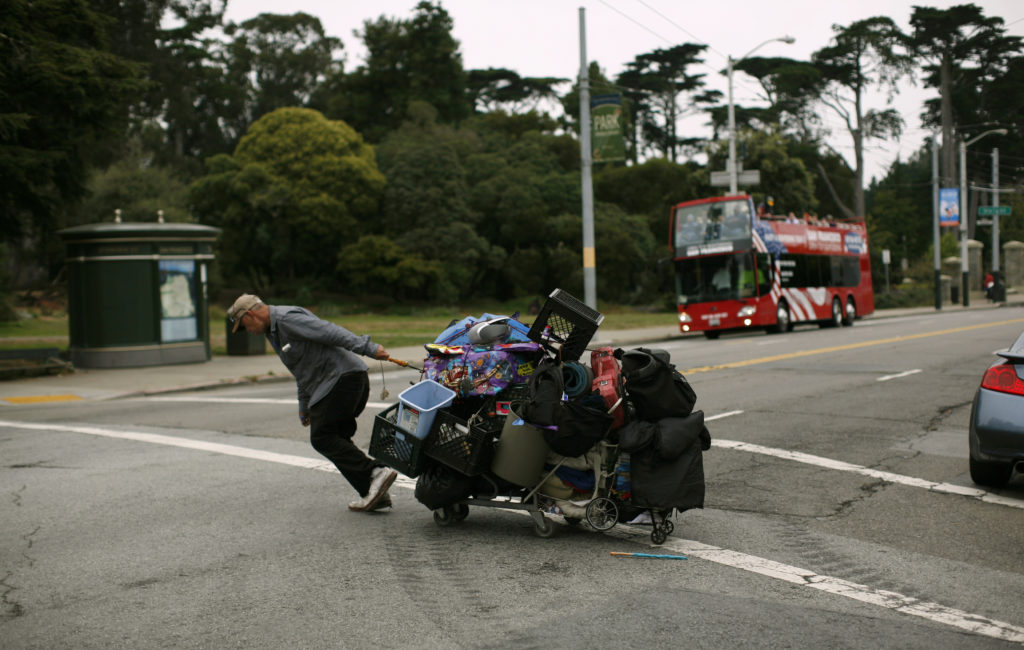 A homeless man hauls his possessions in a shopping cart in the Haight Ashbury neighborhood in San Francisco, California August 22, 2011.  REUTERS/Robert Galbraith  (UNITED STATES - Tags: SOCIETY) - GM1E78N0O3X01