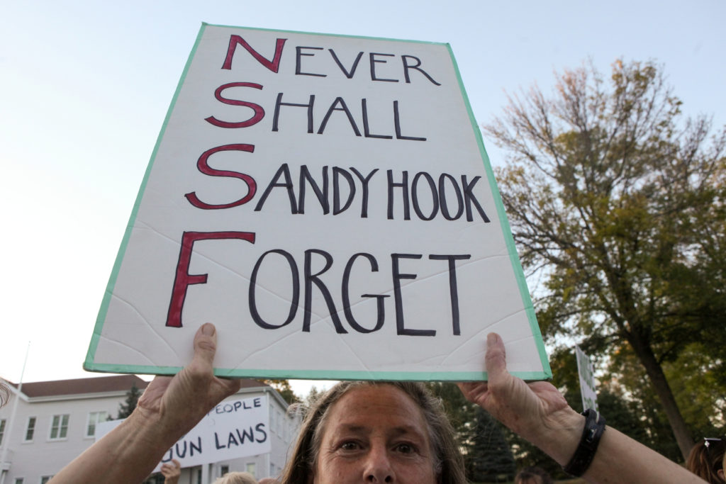 Karen Perrone holds a sign during a solidarity vigil in memory of victims of Las Vegas' Route 91 Harvest music festival mass killing, in Newtown, Connecticut U.S., the site of the 2012 Sandy Hook school shooting, October 4, 2017. REUTERS/Michelle McLoughlin