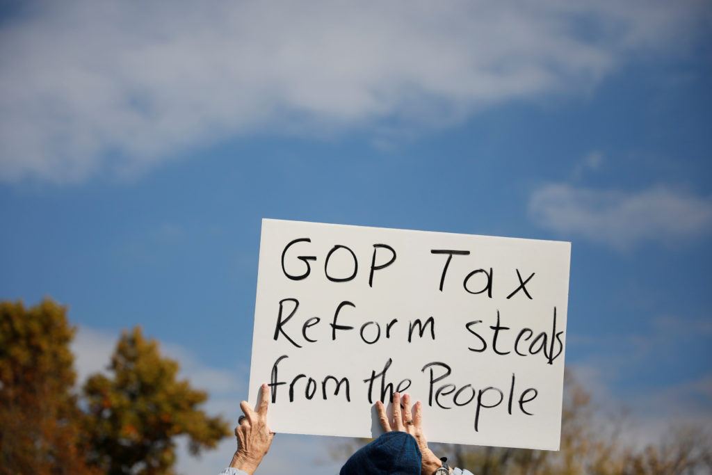 A demonstrator holds a sign during a rally against the Republican tax bill on Capitol Hill in Washington, U.S., November 15, 2017. REUTERS/Aaron P. Bernstein - RC18470B1000