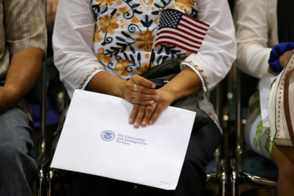 An attendee holds her new country's flag and her naturalization papers as she is sworn in during a U.S. citizenship ceremony in Los Angeles, U.S., July 18, 2017. Picture taken July 18, 2017. REUTERS/Mike Blake - RC1985AD4490