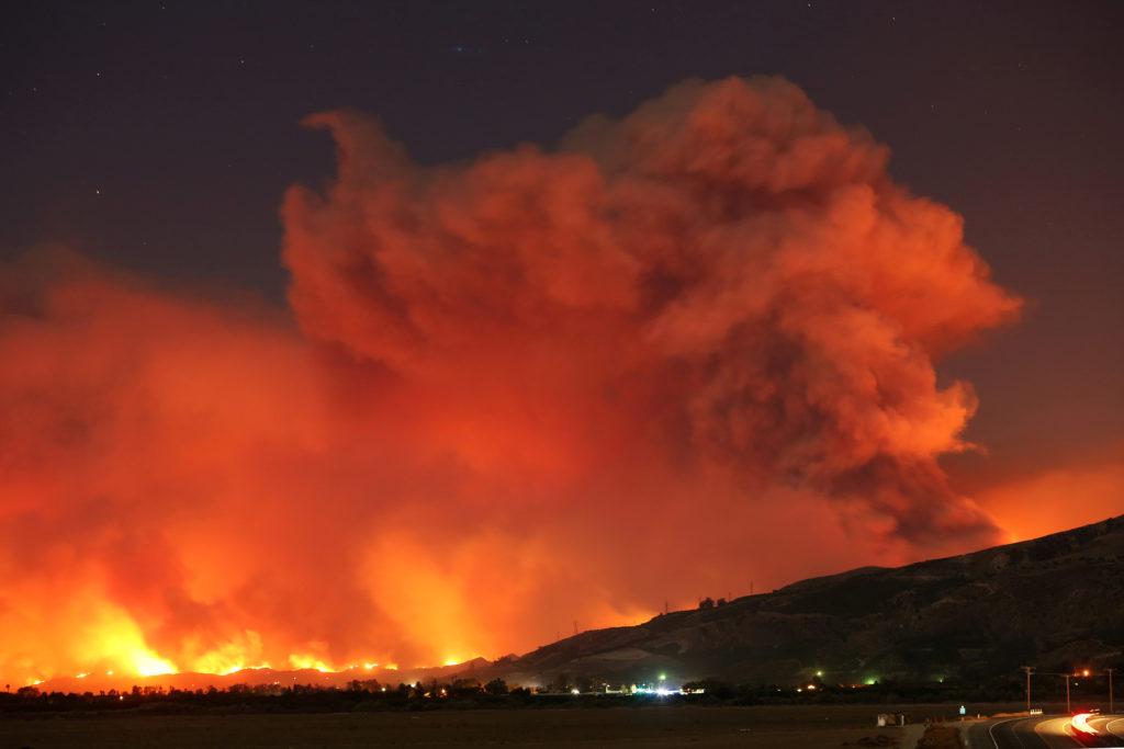 Smoke rises into the night sky as strong winds push the Thomas Fire across thousands of acres near Santa Paula