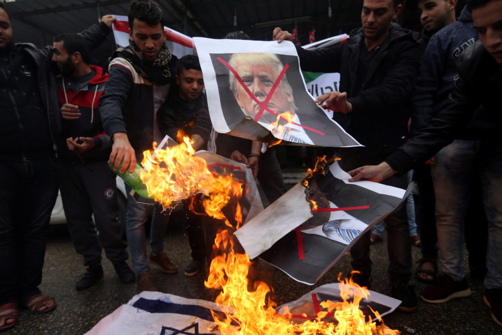 Palestinians burn posters depicting U.S. President Donald Trump and Israeli Prime Minister Benjamin Netanyahu during a protest against the U.S. intention to move its embassy to Jerusalem and to recognize the city of Jerusalem as the capital of Israel, in Rafah in the southern Gaza Strip, on Dec. 6. Photo by Ibraheem Abu Mustafa/Reuters