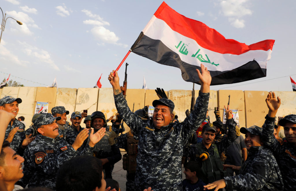 The Iraqi Federal Police wave Iraqi flags as they celebrate victory against the Islamic State militants in West Mosul, Iraq on July 2. Photo by Erik De Castro
