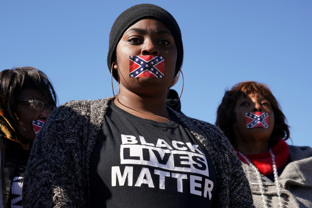 People stand in silent protest with confederate flag stickers covering their mouths during the official opening ceremony for the Mississippi Civil Rights Museum in Jackson, Mississippi, U.S., December 9, 2017. REUTERS/Carlo Allegri - RC1FFF824C30