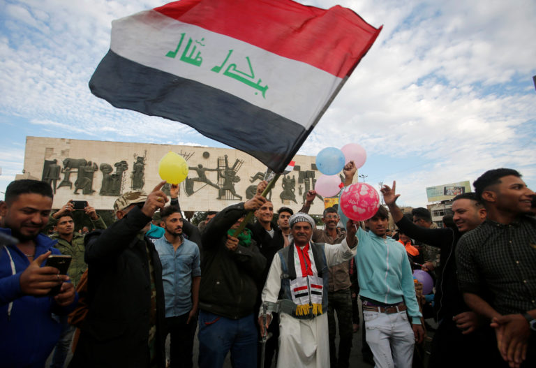 Iraqi people gather as they celebrate the final victory over the Islamic State at Tahrir Square in Baghdad