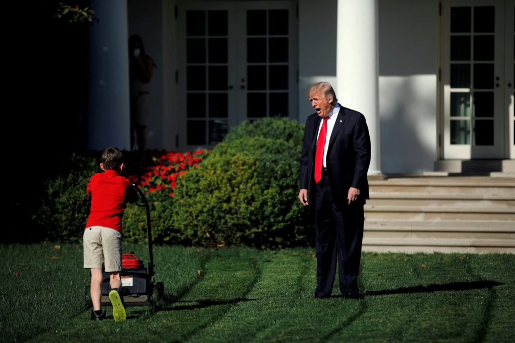 President Donald Trump tries to get the attention of 11-year-old Frank Giaccio, who is engrossed in cutting the Rose Garden grass at the White House on Sept. 15. Photo by Carlos Barria/Reuters