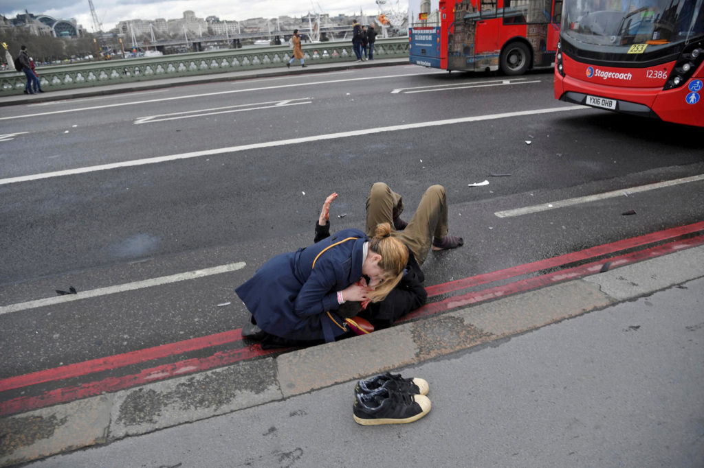 A woman helps an injured person after a man drove a car into pedestrians on Westminster Bridge in London on March 22. Photo by Toby Melville/Reuters