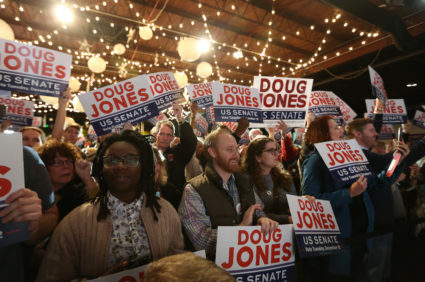 Supporters of Democratic Alabama U.S. Senate candidate Doug Jones listens to Jones as he speaks at a rally at Old Car Heaven in Birmingham, Alabama, U.S. December 11, 2017. REUTERS/Marvin Gentry - RC154BFE04B0