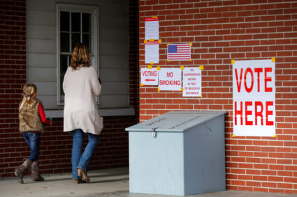 Anna Atkinson walks into a polling station with her 8-year-old daughter Tori, in Gallant, Alabama, U.S., December 12, 2017. REUTERS/Jonathan Bachman - RC1313494170