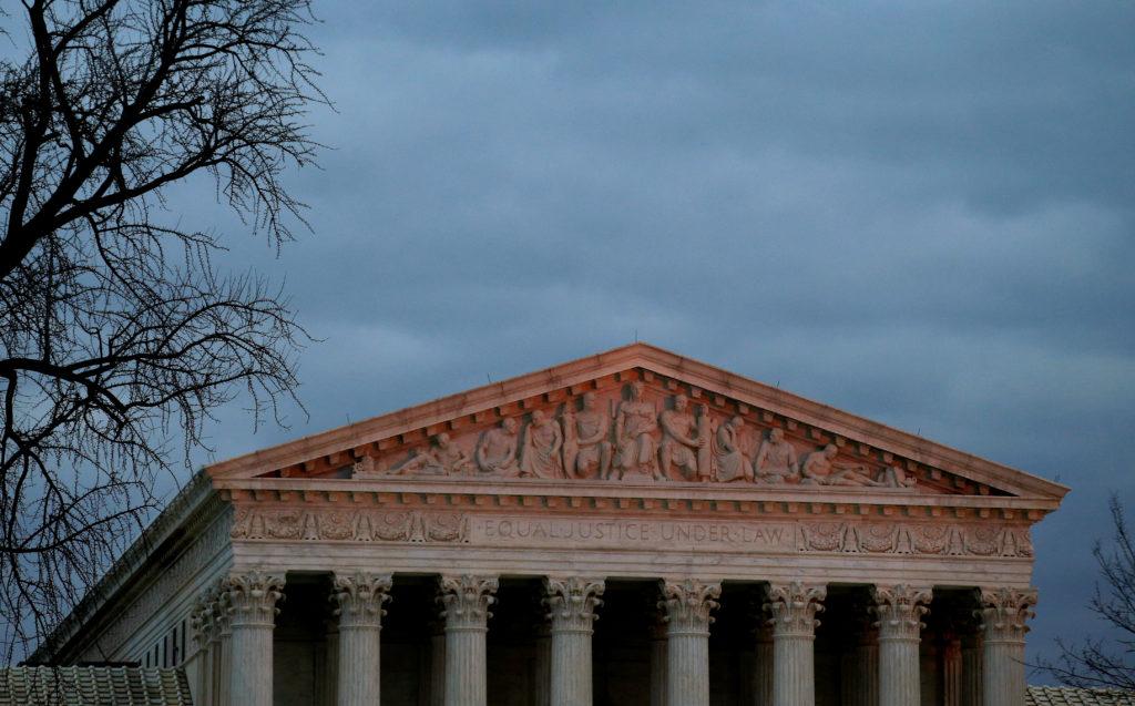 The top of U.S. Supreme Court building is lit at dusk in Washington, U.S., December 18, 2017. REUTERS/Joshua Roberts - RC13542D7C60