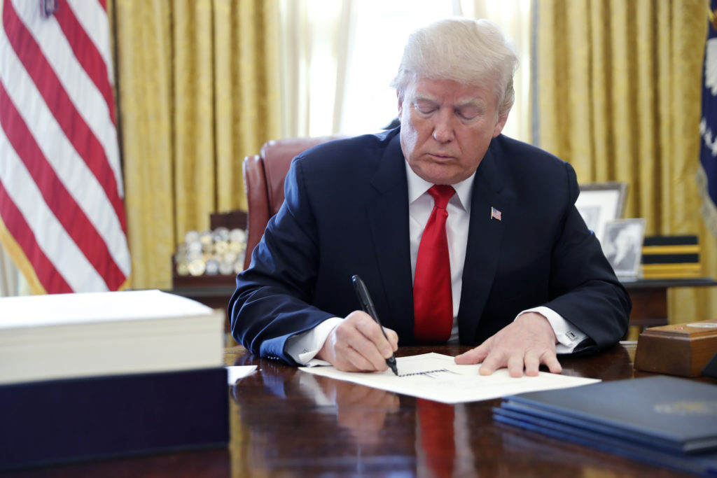 U.S. President Donald Trump signs the $1.5 trillion tax overhaul plan into law in the Oval Office of the White House on December 22, 2017. Photo by Jonathan Ernst/Reuters