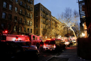 New York Police Department officers and Fire Department of New York personnel work on the scene of an apartment fire in Bronx, New York. Photo by Eduardo Munoz/Reuters
