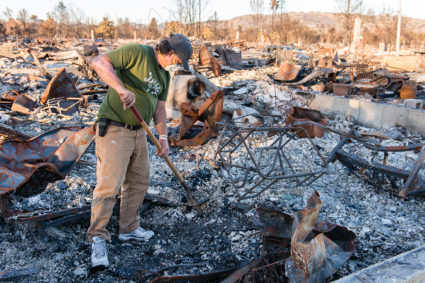 """Ed Corn wears a mask as he sifts through the ashes of the home he shared with his paraplegic roommate in Santa Rosa's Coffey Park neighborhood. """"I can definitely taste the toxins in my throat and the back of my tongue,"""" he said. Photo by Heidi de Marco/KHN"""