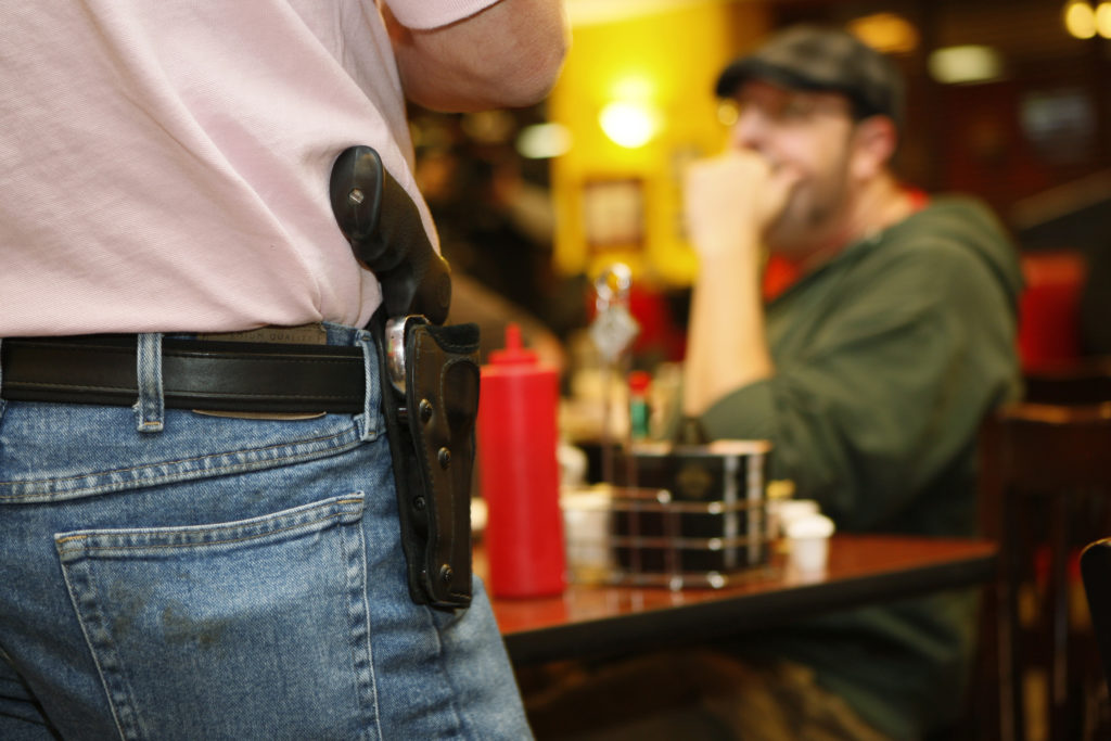 Bryan Hull, founding director of the Oklahoma Open Carry Association (OKOCA), wears an unconcealed side arm as he addresses OKOCA members gathered at Beverly's Pancake House in Oklahoma City November 1, 2012. A new Oklahoma law took effect November 1 allowing anyone with a concealed weapon license to carry their firearms openly in a holster or belt. REUTERS/Bill Waugh (UNITED STATES - Tags: SOCIETY POLITICS CRIME LAW) - GM1E8B116QY01