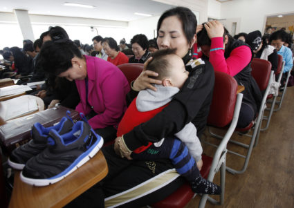 A North Korean defector (R) holds her son as she prays for human rights in North Korea during a service at Saetu Church in Seoul April 25, 2010. The North Korean Refugees' Church Coalition, consisting of eight Christian churches for North Korean defectors, held the first joint prayers for the remaining North Koreans on Sunday. REUTERS/Jo Yong-Hak (SOUTH KOREA - Tags: POLITICS RELIGION) - GM1E64P1BP701