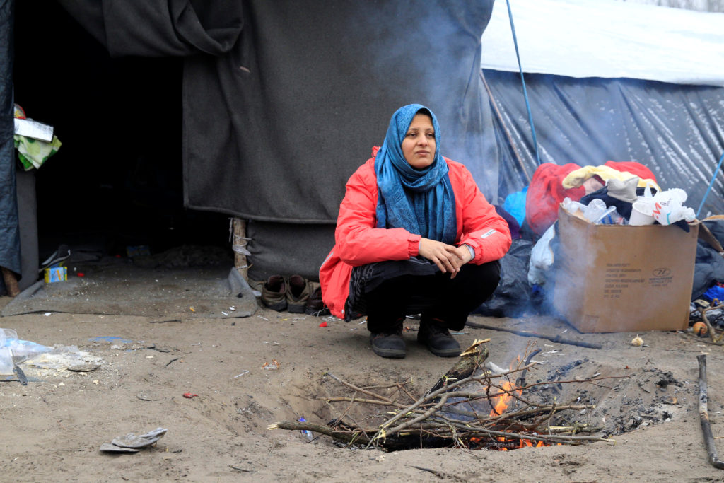 A migrant woman warms herself by the fire at a makeshift camp in the transit zone on the Serbian-Hungarian border near Horgos, Serbia January 9, 2017. Photo by Bernadett Szabo/REUTERS