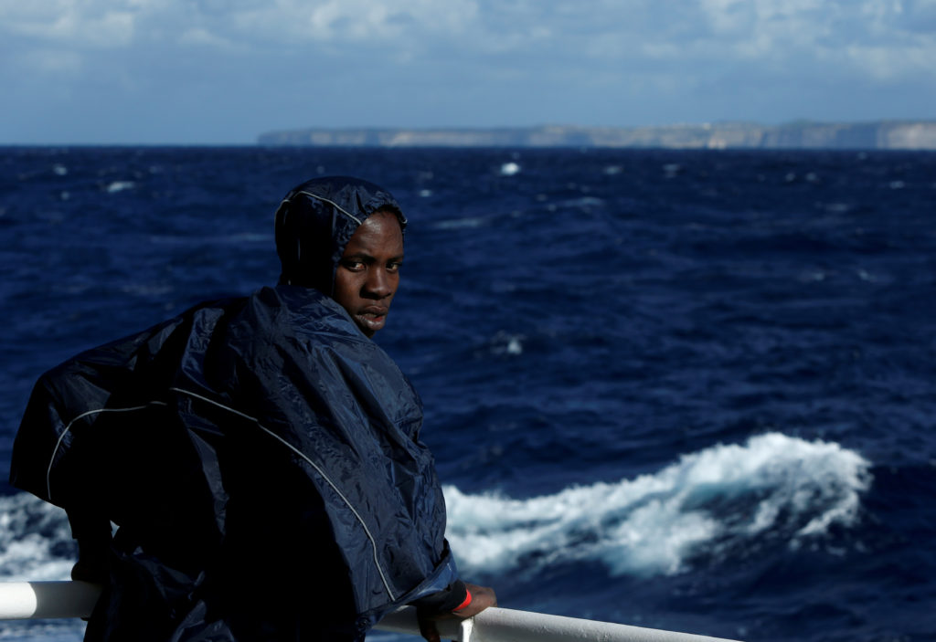 A migrant stands on the deck of the MV Aquarius, a search and rescue ship run in partnership between SOS Mediterranee and Medecins Sans Frontieres, as it passes the Maltese island of Gozo while making its way to the Italian island of Sicily after rescue operations in the central Mediterranean off the coast of Libya, December 17, 2017. Photo by Darrin Zammit Lupi/REUTERS