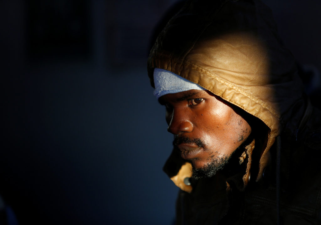 A migrant waits for the MV Aquarius, a search and rescue ship run in partnership between SOS Mediterranee and Medecins Sans Frontieres, to enter Pozzallo on the island of Sicily, Italy, December 18, 2017. Photo by Darrin Zammit Lupi/REUTERS