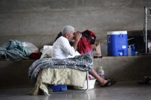 A man who lost his home during Hurricane Maria in September drinks a beverage while sitting on a cot at a school turned shelter during a visit of former U.S. president Bill Clinton (not pictured), in Canovanas, Puerto Rico November 20, 2017. REUTERS/Alvin Baez - RC18C4861620