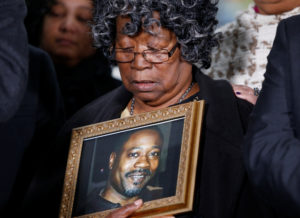 Judy Scott looks over a photo of her son Walter Scott during a news conference after former police officer Michael Slager was sentenced to 20 years in prison, in Charleston, South Carolina, U.S., December 7, 2017. REUTERS/Randall Hill NO RESALES. NO ARCHIVES - RC17B6850B10