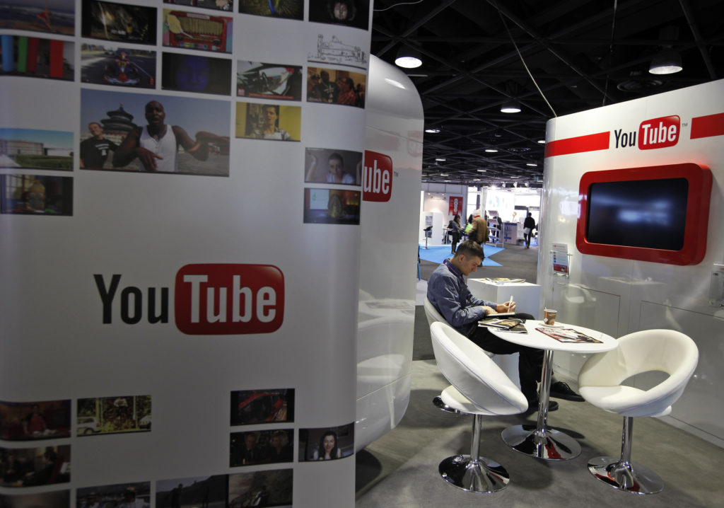A visitor sits at the YouTube stand during the International Record Music Publishing and Video Music Market (MIDEM) in Cannes January 29, 2012. REUTERS/Eric Gaillard (FRANCE - Tags: ENTERTAINMENT BUSINESS) - GM1E81T1OI201