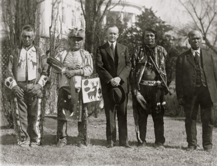 President Calvin Coolidge posed, full-length portrait, standing, facing front, with four Osage Indians, White House in the background, 1925. (Photo by National Photo/Buyenlarge/Getty Images)