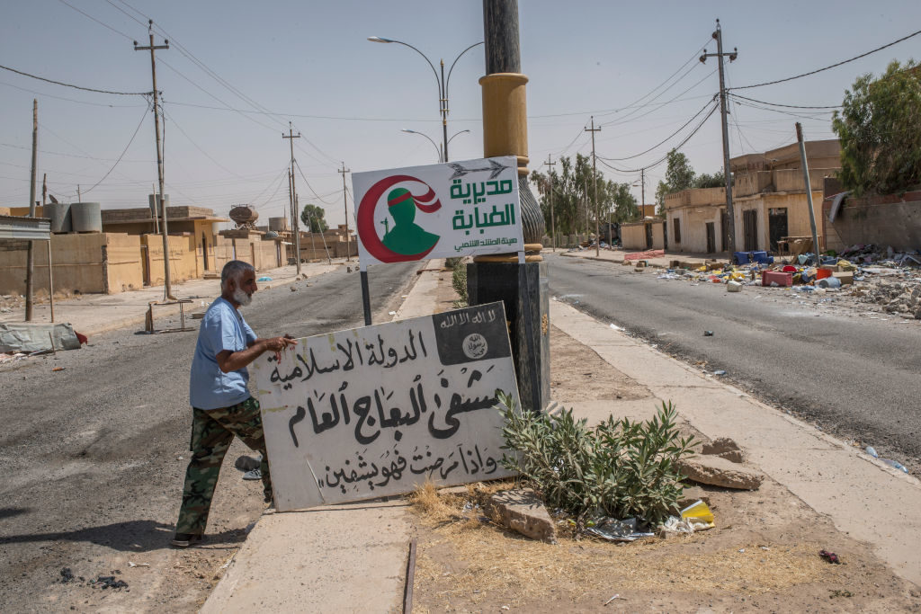 An Iraqi medic takes down an Islamic State sign and replaces it with a Shia militia sign on June 20 in the northwestern Iraq town of Ba'aj near the Iraq-Syria border. Photo by Martyn Aim/Getty Images
