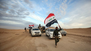 An Iraqi fighter waves the national flag as Iraqi forces and members of the Hashed al-Shaabi (Popular Mobilization Units) advance through Anbar province, 12 miles east of the city of Rawah in the western desert bordering Syria, on Nov. 25, in a bid to flush out remaining Islamic State group fighters. Photo by Ahmad Al-Rubaye/AFP/Getty Images