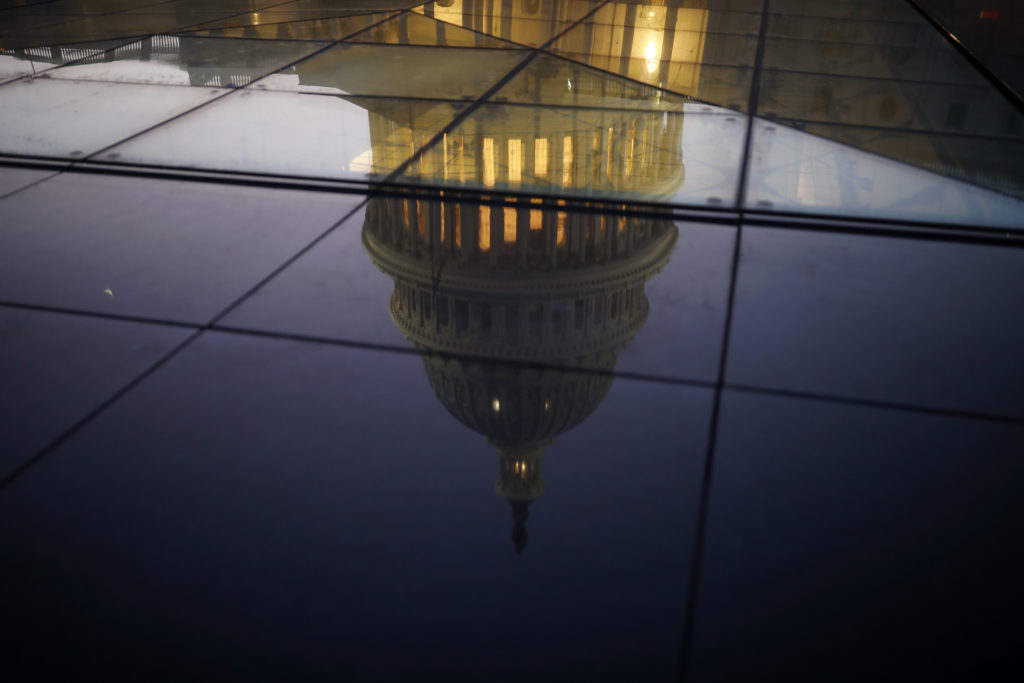 The U.S. Capitol is seen reflected in the windows of the Capitol Visitors Center as lawmakers work to avert a government s...