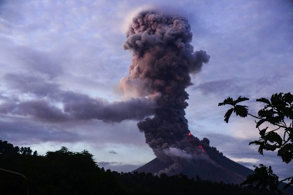 The Mayon volcano spews lava as it continues to erupt, as seen from Daraga town, in Albay province, south of Manila on January 23, 2018. Intense lava fountains shot like fireworks up to 2,300 feet into the air above Mayon, the Philippines' most active volcano, on January 23 as showering debris turned morning skies dark and spread fear among anxious residents. Photo by LINUS ESCANDOR II/AFP/Getty Images