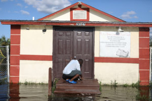 Pastor Louicesse Dorsaint opens the door to his church Haitian United Evangelical Mission which was damaged by flooding from Hurricane Irma in Immokalee, Florida, U.S. September 12, 2017. REUTERS/Stephen Yang - RC1ED9A2B240