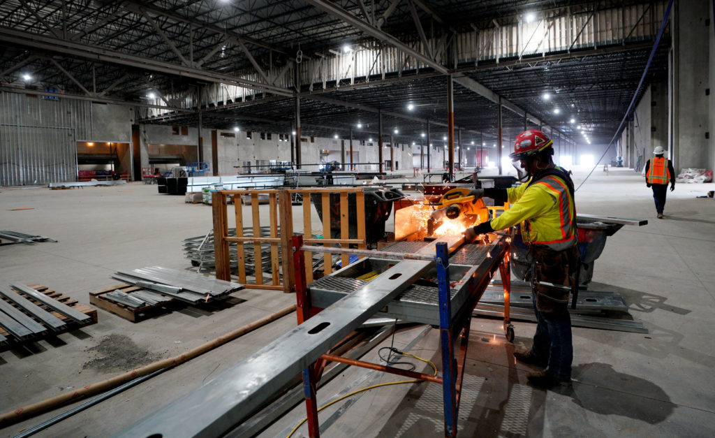 A worker cuts a metal stud in the convention center part of the Gaylord Rockies Resort & Convention Center under construction outside Denver, Colorado, U.S. November 3, 2017. REUTERS/Rick Wilking - RC12B873D450