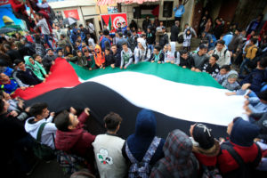Students hold a Palestinian flag inside the Ain el-Hilweh refugee camp near Sidon, southern Lebanon in December 2017. Photo by Ali Hashisho/Reuters