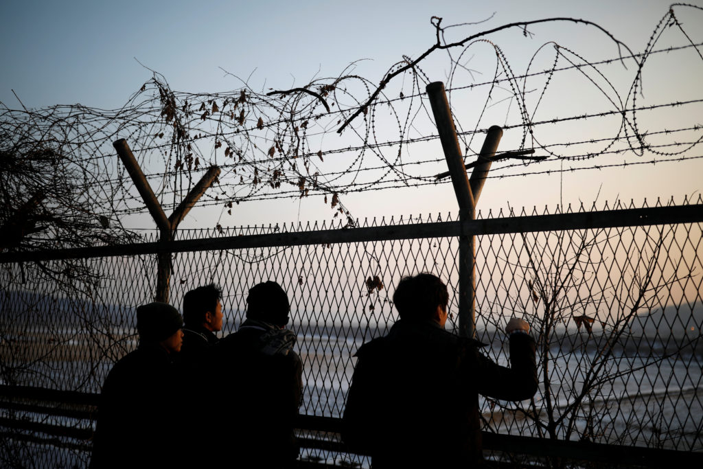 People look toward North Korea through a barbed-wire fence near the demilitarized zone separating the two Koreas, in Paju, South Korea, on Dec. 21. Photo by Kim Hong-Ji/Reuters